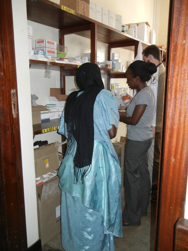 "Vicky dispenses medication and provides education to a caregiver for one of the patients; notice the beautiful outfit- I thought this woman might have ""dressed up"" to come to the hospital but I was told that this is her normal, everyday traditional garment."