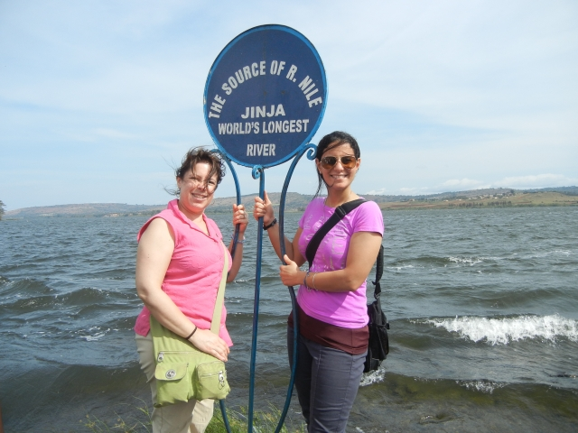 KarenBeth and Sammi at the Source of the Nile sign.  Behind us lies Lake Victoria and in front of us, towards the bottom left-hand corner of the picture flows the Nile River.