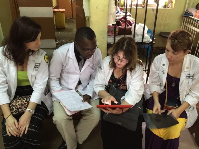 Dr. Bohan reviews a patient chart with Kristen, David, the leader of the Ugandan Pharmacy Interns, and Amanda on the Stanfield Pediatric Ward