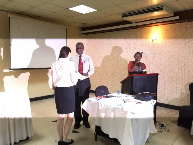 Stacy recieves a certificate for her platform presentation from the Patron of the JISSC, Dr. Bwana