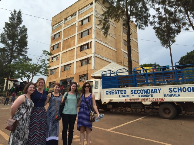 The large building behind the girls is the main school building housing both classrooms and a dormitory.