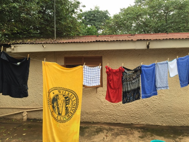 Hanging laundry to dry. My house is in the background. The blue wash bucket is on the cement.