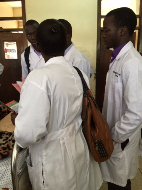 4th Year students at the bedside of a patient at Mulago Hospital as they interview the patient to learn about the medications the patient was on at home.
