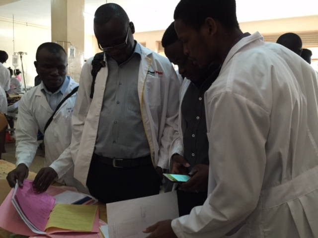 4th Year students consult with each other while they review a patient's medical record at Mulago Hospital