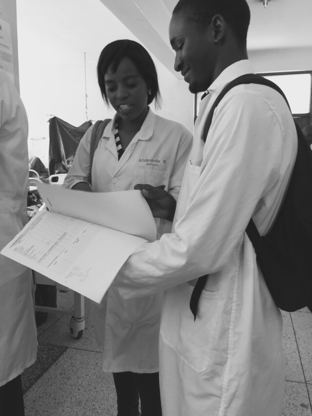 4th Year students consult with each other while they review their notes from a patient interview at Mulago Hospital